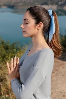 Mulher meditando na natureza, vista lateral
