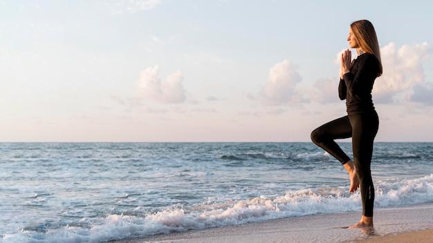 Mulher meditando na praia com espaço de cópia