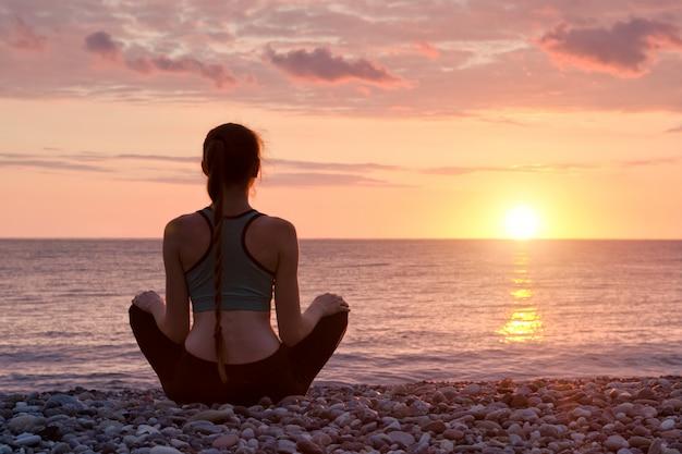 Mulher meditando na praia. pôr do sol
