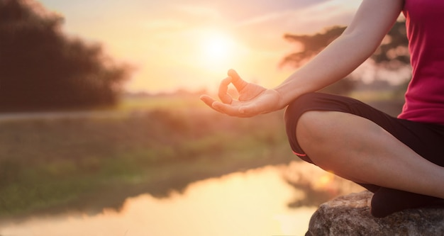 Mulher meditando no lago