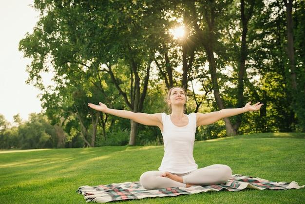 Mulher meditando no parque da cidade