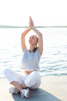 Mulher meditando, perto, água