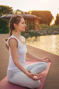 Mulher meditando perto do lago
