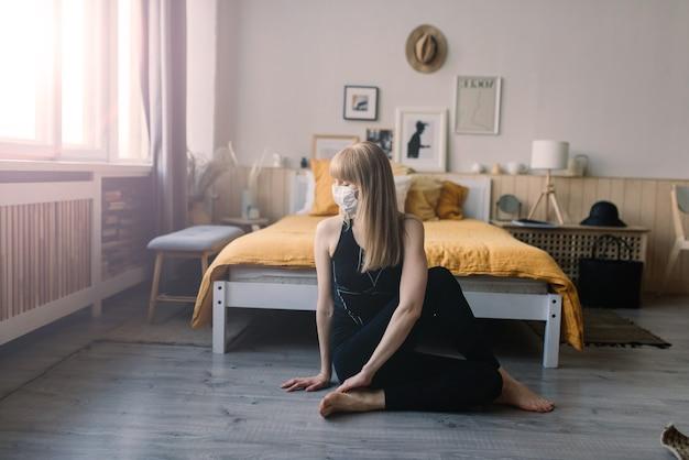 Mulher meditando usando uma máscara médica para se proteger do vírus corona, posição de ioga na casa do tapete