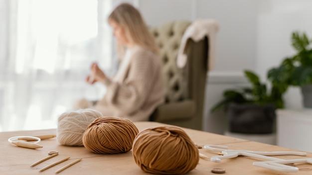 Mulher meio desfocada tricotando dentro de casa