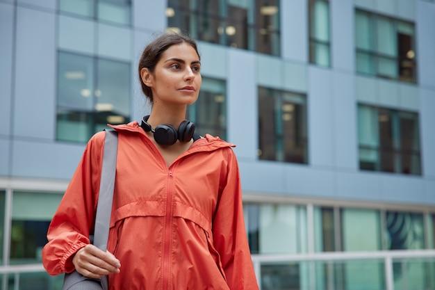Mulher melhora seu bem-estar desenvolve agilidade física e coordenação corporal adequada encontra lugar para se exercitar ao ar livre com prédio moderno atrás absorve vitamina d à luz do dia