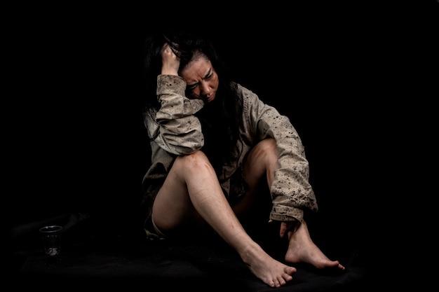 Mulher mendiga suja sentada no chão em blackground