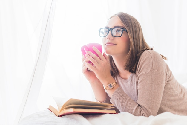 Mulher, mentindo cama, com, livro copo café, daydreaming