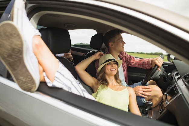 Mulher, mentindo carro, com, dela, pés, saída, de, janela carro, com, seu, namorado, dirigindo