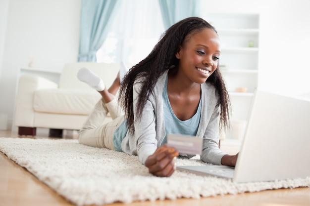 Mulher, mentindo chão, com, dela, laptop, fazendo compras online