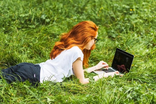 Mulher, mentindo, ligado, capim brilhante, com, laptop