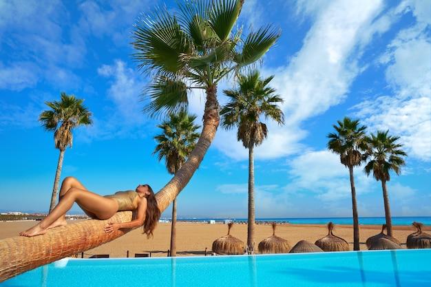 Mulher, mentindo, ligado, piscina, curvado, tronco árvore palma