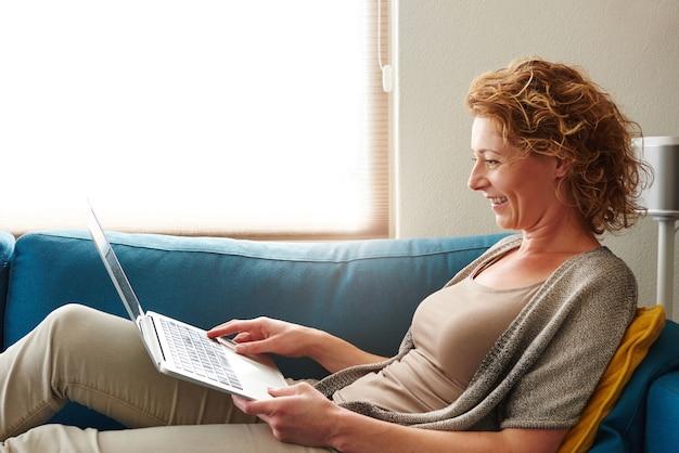 Mulher, mentindo, ligado, sofá, com, laptop, sorrindo