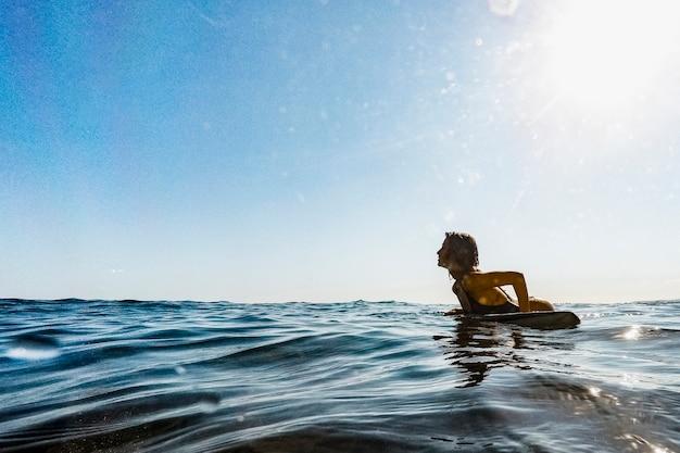 Mulher, mentindo, ligado, surfboard, em, água