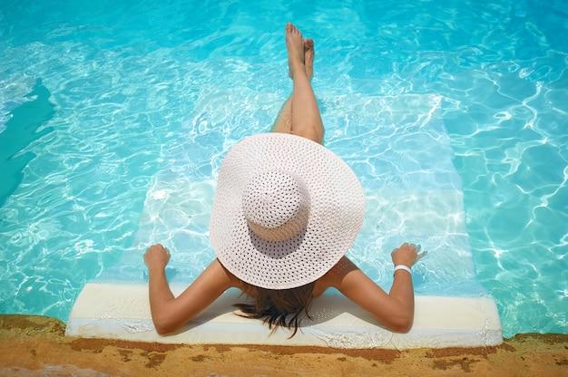 Mulher, mentindo, ligado, um, lounger, em, piscina, em, hotel