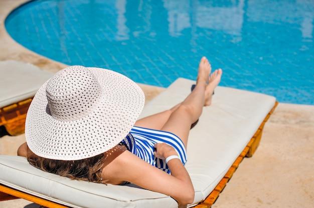 Mulher, mentindo, ligado, um, lounger, por, a, piscina, em, a, hotel