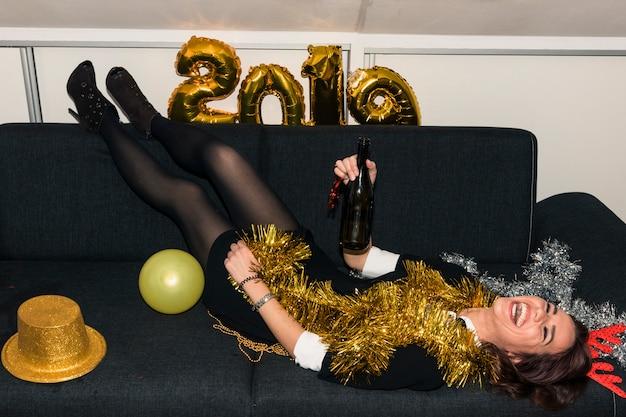 Mulher, mentindo sofá, com, garrafa champanha