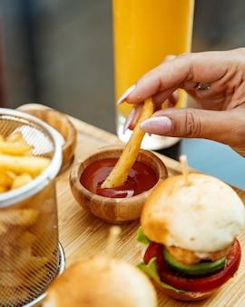Mulher mergulhando batatas fritas em ketchup