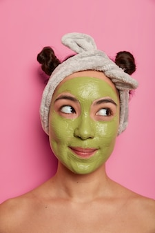 Mulher mestiça, bonita e atenciosa se preocupa com a pele e a tez, aplica máscara verde nutritiva no rosto, usa bandana, dois coques de cabelo, fica de pé com os ombros nus, concentrada de lado. procedimentos de spa