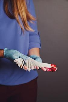 Mulher mestre em salão de beleza realiza teste de cores de esmaltes