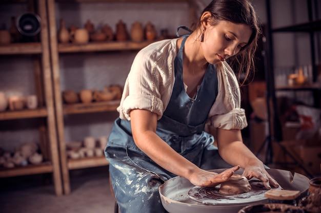 Mulher mestre potter fazendo pote de cerâmica na roda de oleiro. produção artesanal. fechar-se.