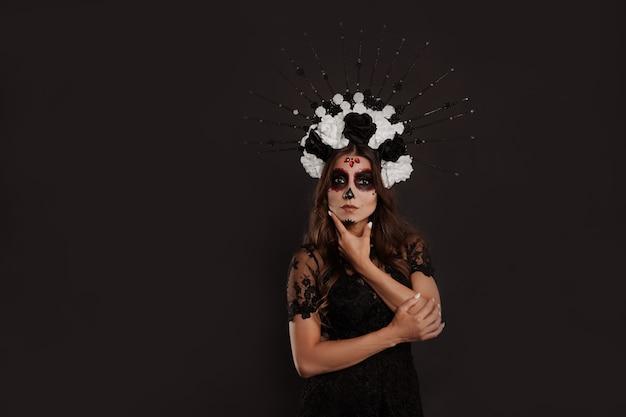 Mulher mexicana com roupa preta especial usa maquiagem profissional com caveira de argila branca para parecer assustadora