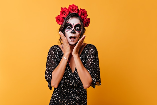 Mulher mexicana emocional de cabelos escuros com flores na cabeça e faz cara de choque se tocando com as mãos