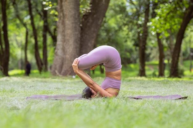 Mulher mexicana fazendo exercícios de ioga no parque, na grama verde