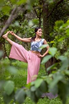 Mulher mexicana fazendo ioga com posturas diferentes em um parque ao ar livre com grama e árvores