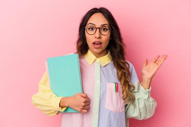 Mulher mexicana jovem estudante isolada em fundo rosa surpresa e chocada.