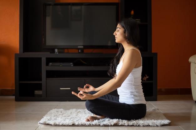Mulher mexicana meditando em casa