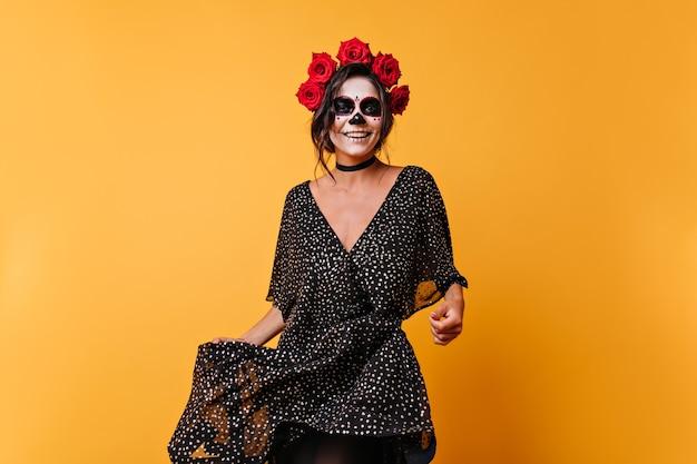 Mulher mexicana positiva dançando com um sorriso no rosto pintado. retrato de uma menina bonita com cabelos ondulados em estúdio laranja.