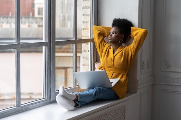 Mulher milenar afro-americana relaxada com penteado afro usa casaco de lã amarelo, sentada no parapeito da janela, descansando, fazendo uma pausa do trabalho no laptop, pensando e olhando para a janela, mãos atrás da cabeça.