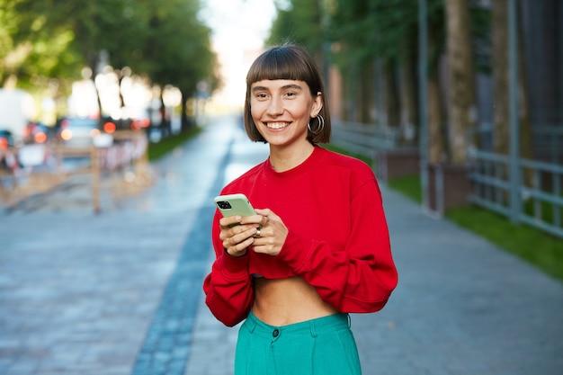 Mulher milenar bonita andando na rua com smartphone, mulher milenar em suéter vermelho elegante tendo smartphone em pé na cidade moderna