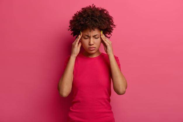 Mulher milenar de pele escura e intensamente pressionada se sente cansada e tonta, mantém as mãos nas têmporas, sofre de uma dor de cabeça insuportável, não suporta a dor, faz caretas de enxaqueca, isolada em uma parede rosada