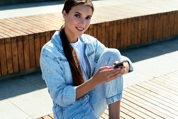 Mulher milenar em roupas jeans, senta-se no banco do parque, comunica-se com amigos, colegas e pais ao telefone. mulher usa o telefone para se comunicar, recebe informações fica em espaço público