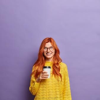 Mulher milenar ruiva segura sorrisos de café para viagem positivamente vestida com um macacão amarelo.