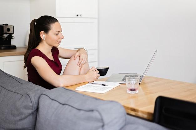 Mulher milenar trabalha em casa. sala cozinha com mesa de madeira e xícara de café. e-learning