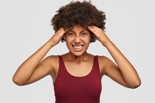 Mulher miserável de pele escura sente desconforto, sofre de dor de cabeça, não consegue focar, cerra os dentes e franze a testa