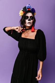 Mulher misteriosa com a imagem de um esqueleto no rosto está tentando arrancar o colar preto do pescoço.