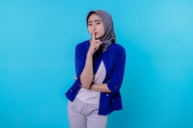 Mulher misteriosa fazendo silêncio gesto desviando o olhar conta segredo usando hijab isolado sobre parede branca