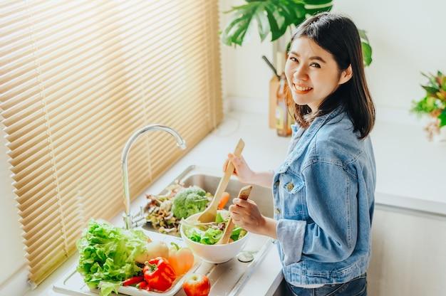 Mulher mistura salada na tigela enquanto cozinha em casa
