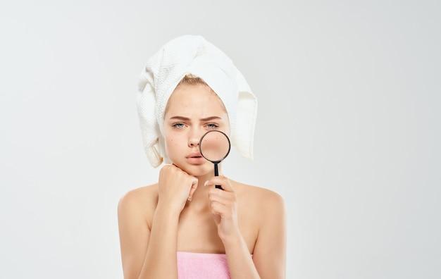 Mulher modelo com lupa na luz e toalha na cabeça.
