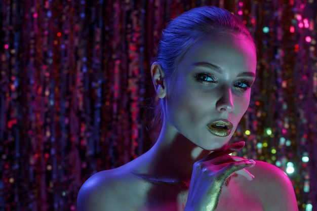 Mulher modelo de alta moda em luzes coloridas de néon, posando no estúdio, clube noturno