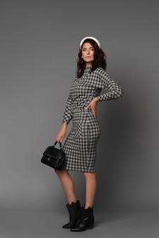 Mulher modelo de meia idade com uma grande figura usando um vestido xadrez na superfície cinza