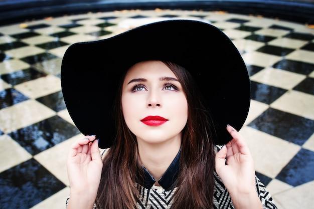 Mulher modelo feliz com um chapéu olhando para cima ao ar livre