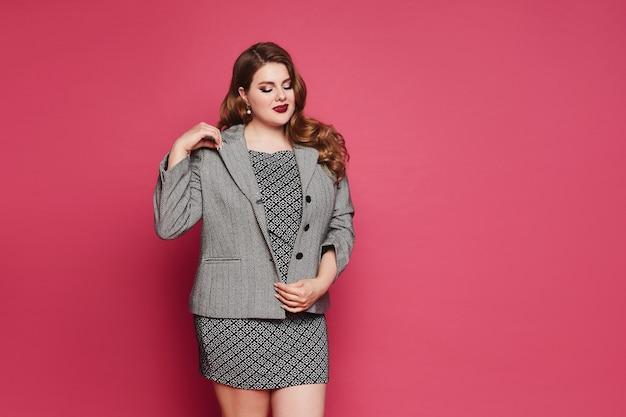 Mulher modelo rechonchuda com maquiagem brilhante em vestido cinza de escritório e poses de blazer no fundo rosa ...