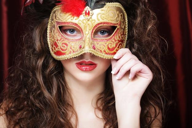 Mulher modelo sexy com máscara de carnaval de baile de máscaras veneziano na festa sobre fundo vermelho de férias.