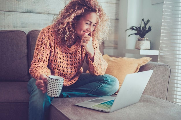 Mulher moderna adulta alegre usa laptop em casa, sentado no sofá, sorrindo e aproveitando a tecnologia de conexão de internet - conceito de trabalho on-line mulheres trabalhando na web - vida de trabalho inteligente