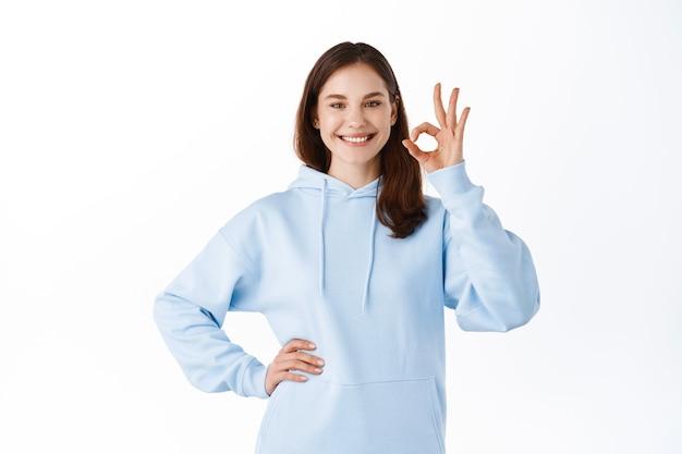 Mulher moderna bonita e impressionada em um moletom azul, aceno em aceitação, mostrar tudo bem, sinal de aprovação, parede branca de pé
